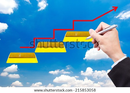 business hand writing pose and red rising arrow walking up gold bars stepping ladder on blue sky idea concept for success and growth - stock photo