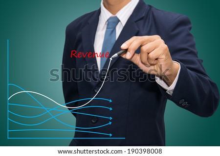 business hand writing revenue graph  - stock photo