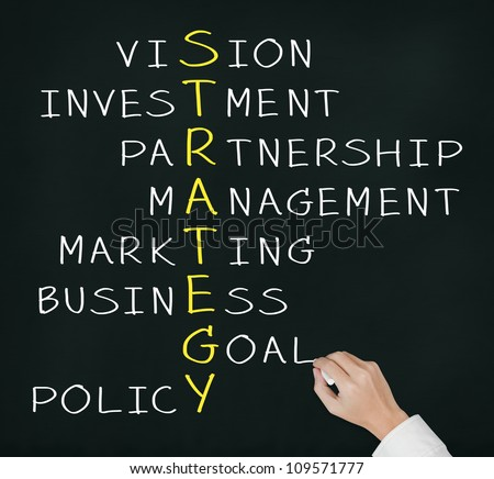 business hand writing strategy concept by crossword of vision, investment, partnership, management, marketing, goal, and policy