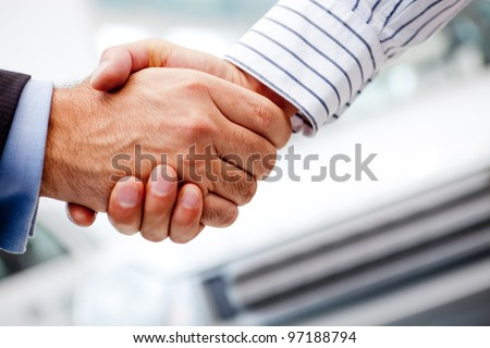 Business handshake after buying a new car - stock photo