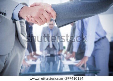 Business handshake against business colleagues discussing about work - stock photo
