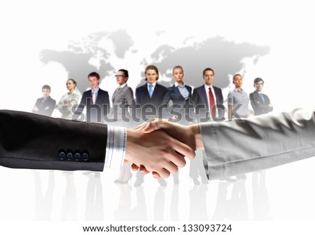 business handshake against white background and standing businesspeople.