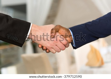 Business handshake and business people. Business people shaking hands corresponding to mutual agreement or deal betweent their companies of firms. - stock photo