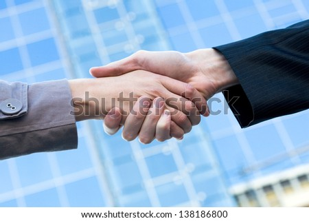 Business handshake at meeting over office building