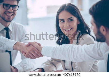 Business handshake. Close-up of two young man shaking hands with smile while sitting at office with their beautiful coworker - stock photo