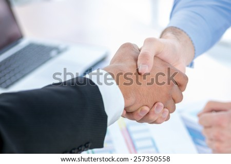 Business handshake. Confident businessman shaking hands with each other. Close-up view of the hands of a businessman in the office of the table in the formal wear. - stock photo