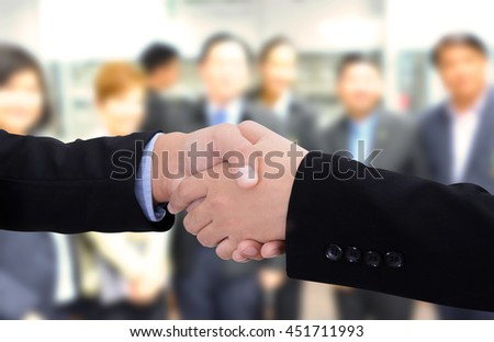 Business handshake in front of business people background.