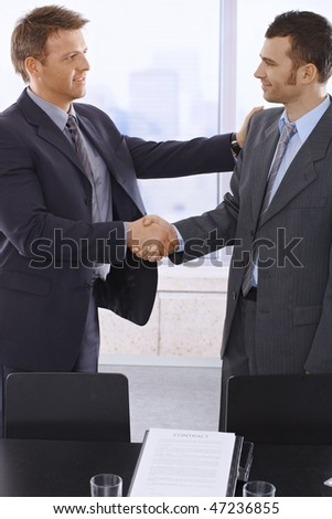 Business handshake in office over signed contract.