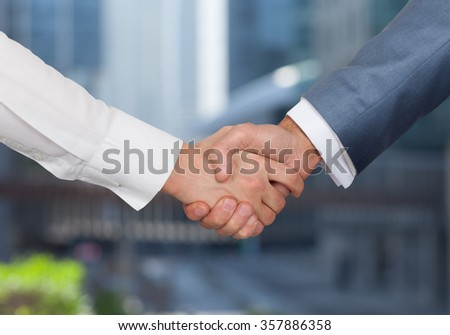 Business handshake of two business people on the background of office building - stock photo
