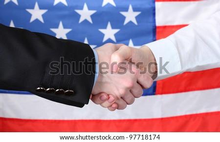 Business handshake on american flag background - stock photo