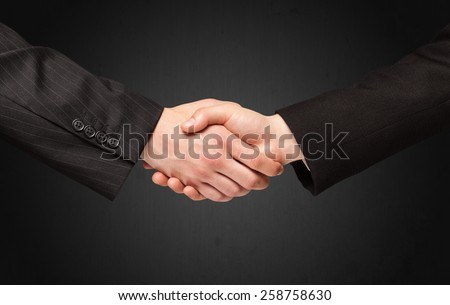 Business handshake on black background - stock photo