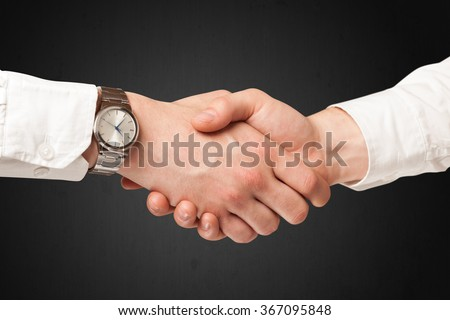 Business handshake on black background - stock photo