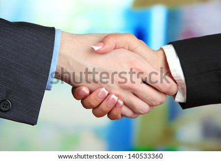 Business handshake on bright background - stock photo