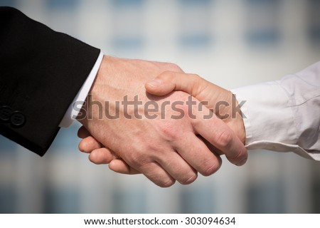 Business handshake on bright background. Photo of handshake of business partners after signing promising contract. - stock photo