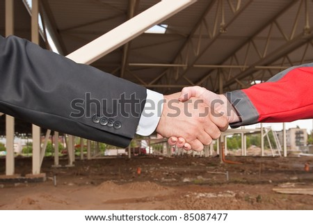 Business handshake on construction site of shopping center - stock photo