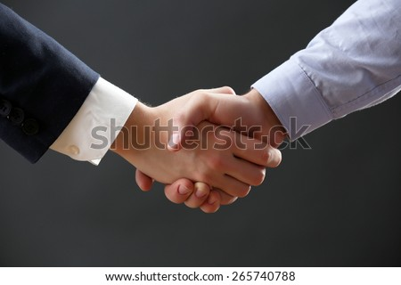 Business handshake on dark background - stock photo