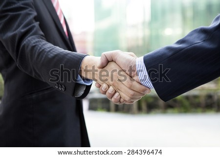 Business handshake on modern city - stock photo