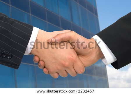 business handshake on modern office building, both files are from photographers portfolio