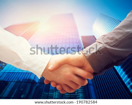 Business handshake on modern skyscrapers background. Deal, success, contract, cooperation concepts  - stock photo