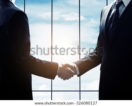 business handshake on sky background