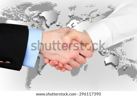 Business handshake on world map background - stock photo