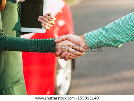 Business handshake to close the deal after buying a car, between a man and a woman - stock photo