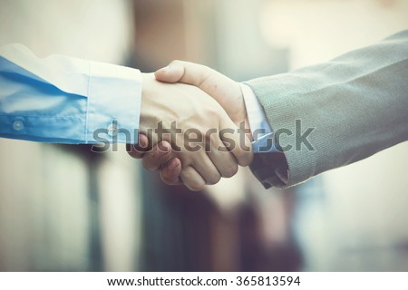 Business handshake. Two businessman shaking hands (Vintage tone) - stock photo