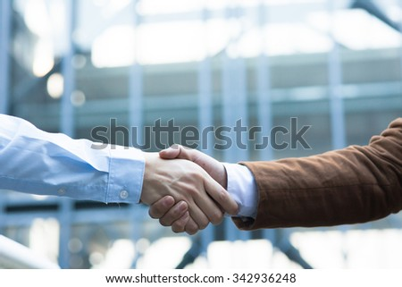Business handshake. Two businessman shaking hands with each other outside