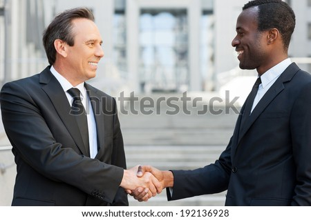 Business handshake. Two cheerful business men shaking hands while standing outdoors - stock photo