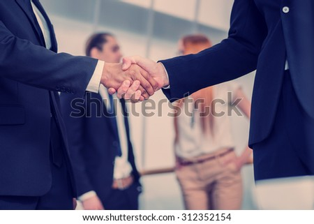 Business handshake. Two successful businessman standing at the table looking at each other shaking hands - stock photo