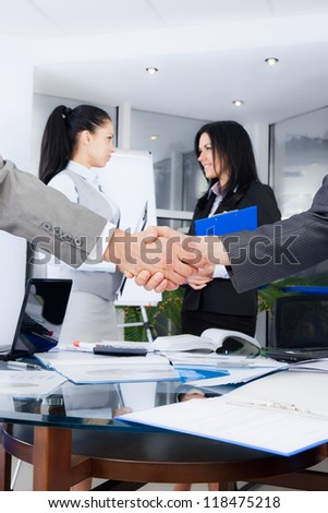 Business handshake with business people on background, colleagues shaking hands during meeting after signing agreement in office - stock photo