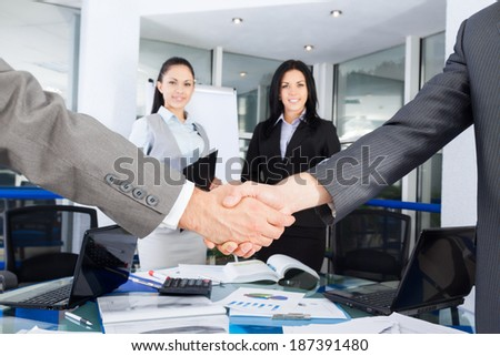 Business handshake with business people on background, colleagues shaking hands during meeting after signing agreement in office