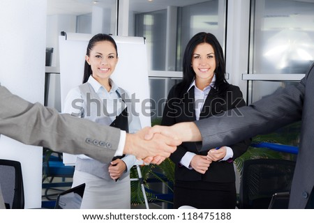 Business handshake with business people smile on background, colleagues shaking hands during meeting after signing agreement in office - stock photo
