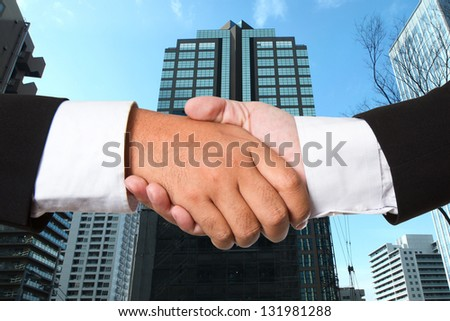 Business handshake with construct background - stock photo