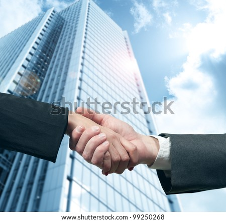 Business handshake with modern office skyscraper - stock photo