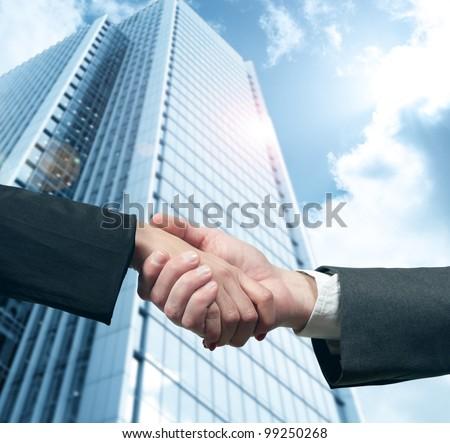 Business handshake with modern office skyscraper - stock photo