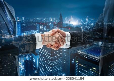 Business handshake with night scene city in background - stock photo