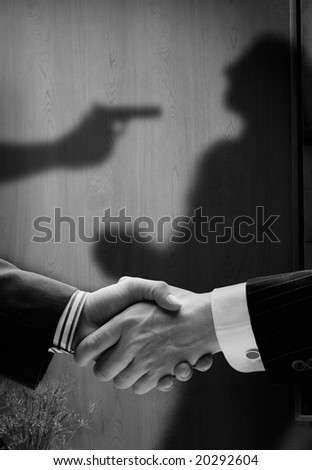 business handshake with shadows behind showing  real intention, with a man being shot by the other - stock photo