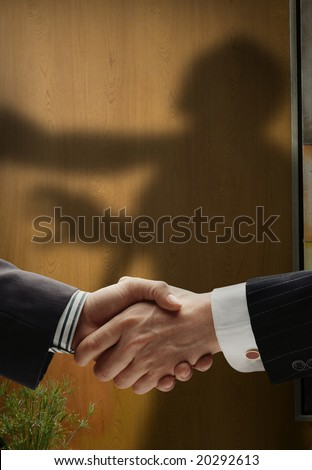 business handshake with shadows behind showing  real intentions, showing a man being choked by the neck - stock photo