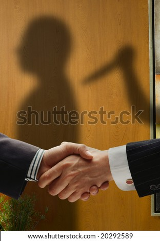 business handshake with shadows behind showing  real intentions, showing a man being stabbed in the back - stock photo