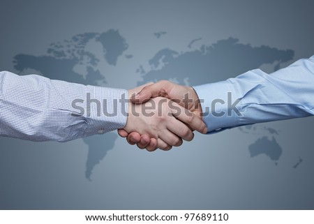 Business handshake with world map in the background - stock photo