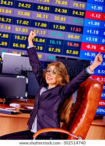 Business happy woman with  stock exchange board hands up in office. - stock photo
