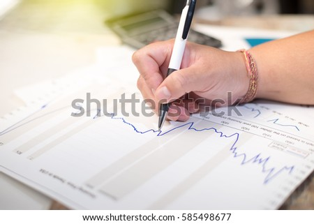 Business holding pen and think with chart and calculator