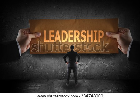Business holding sign leadership on paper - stock photo