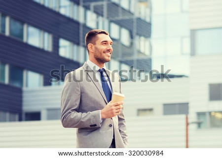 business, hot drinks and people and concept - young serious businessman with paper coffee cup over office building - stock photo