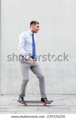 business, hot drinks and people and concept - young smiling businessman riding on skateboard outdoors - stock photo
