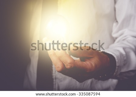 Business idea and vision, businessman holding light bulb, concept of new ideas, innovation, invention and creativity, retro toned image, selective focus. - stock photo