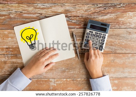 business idea, education, people and technology concept - close up of female hands with calculator, pen and lighting bulb drawing in notebook on table - stock photo