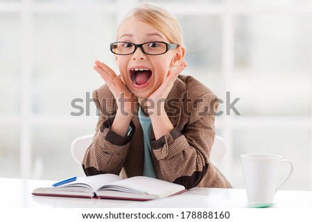 Business in fun. Cheerful little girl in glasses and formalwear sitting at the table and grimacing  - stock photo