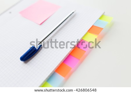 business, information, memo, management and education concept - close up of notebook or organizer with blank tags and pen on office table - stock photo